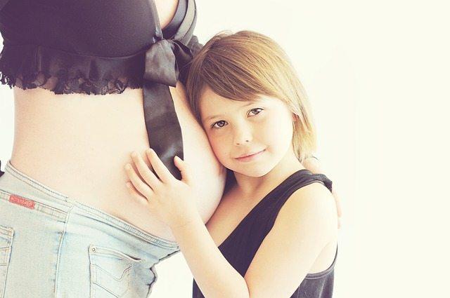 ילדה מאזינה לתינוק בבטן הריונית - כאבי גב בהיריון יש טיפול