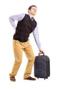 גבר עם מזוודה כבדה סובל מכאב גב תחתון