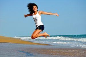 אשה שמחה קופצת על חוף ים - פעילות גופנית נגד כאבי גב תחתון